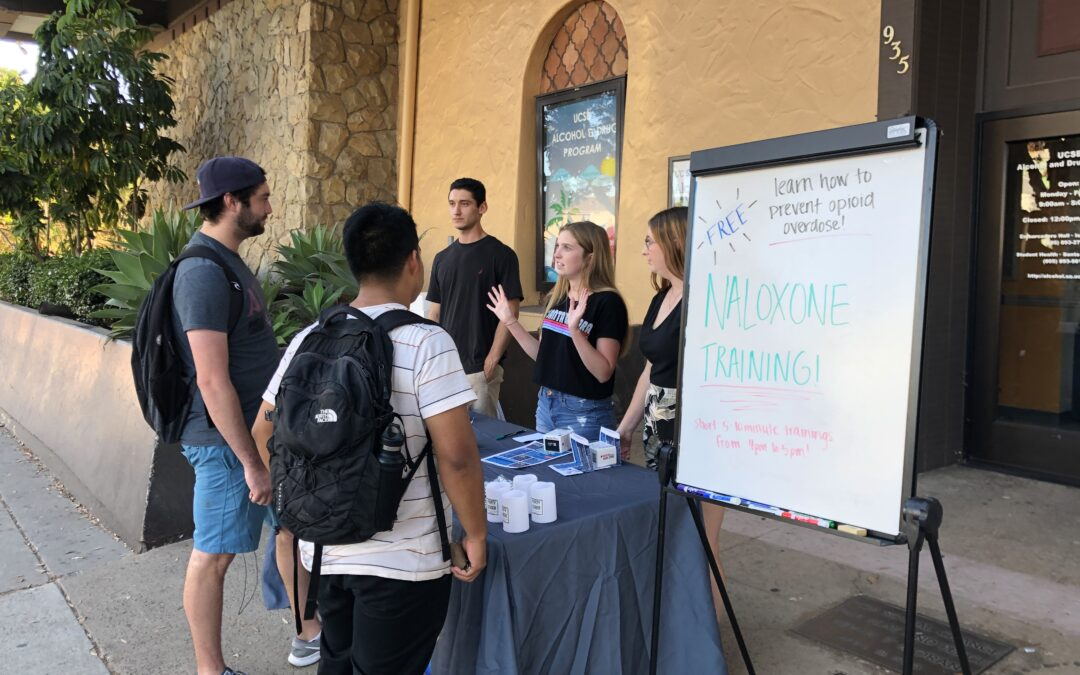 Picture of Angie Bryan handing out naloxone at UC Santa Barbara